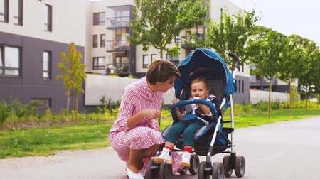 wozek dzieciecy : mother kissing son eating chocolate in stroller