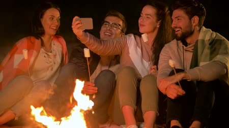 костра : friends taking selfie at night camp fire Стоковые видеозаписи