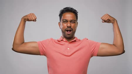 evet : indian man showing biceps over grey background