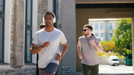 playlist : male friends with headphones running outdoors Stock Footage