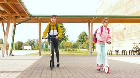 pré adolescente : children riding scooters at school yard