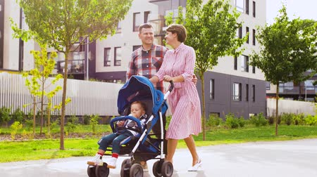 droga : family with baby in stroller walking along city