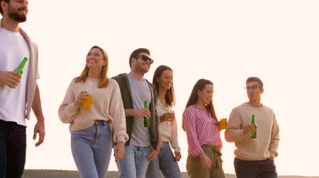 limonada : friends with non alcoholic drinks walking on beach