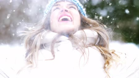 xマス : happy young woman throwing snow in winter forest