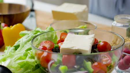 tofu : woman cooking vegetable salad with feta and oil