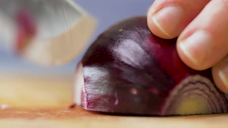 prepare food : hands with knife chopping red onion at home