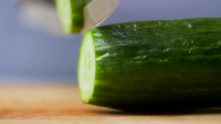 vegetarianismo : kitchen knife chopping cucumber on cutting board