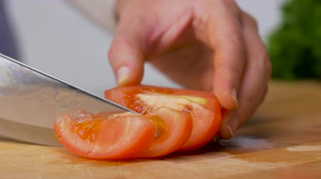 vegetarianismo : woman chopping tomato with kitchen knife at home