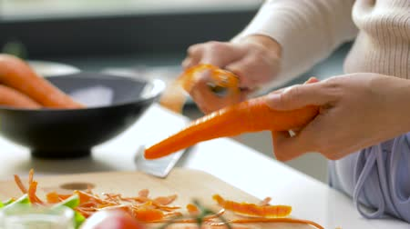tápanyagok : hands peeling carrot with vegetable peeler