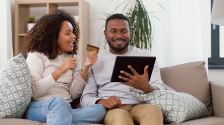 cash free : couple with tablet pc and credit card at home