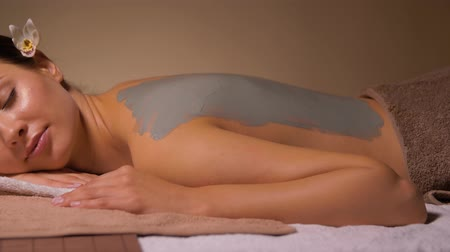 глина : woman with blue clay mask on her back at spa