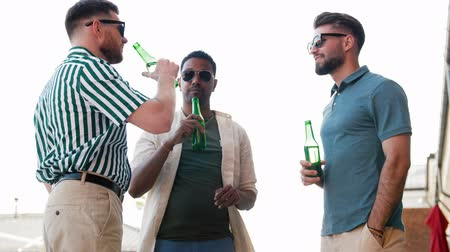 cheers : happy male friends drinking beer at rooftop party Stock Footage