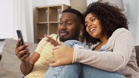 afro americana : happy couple with smartphone moving to new home