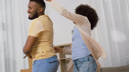 relocate : happy couple moving to new home and dancing