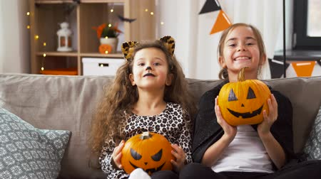 yaban kedisi : girls in halloween costumes with pumpkins at home Stok Video