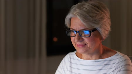 senior lifestyle : happy senior woman with laptop at home in evening