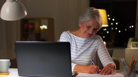 factuur : happy senior woman with laptop at home in evening