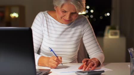 factuur : senior woman filling tax form at home in evening
