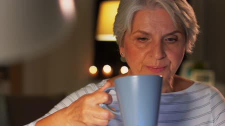 caneca : senior woman with laptop drinking coffee at home