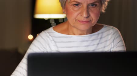 em casa : senior woman with laptop at home in evening