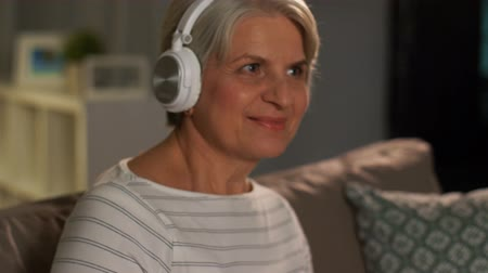 naladit : senior woman in headphones listening to music Dostupné videozáznamy
