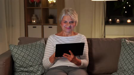 свечи : happy senior woman with tablet pc at home at night Стоковые видеозаписи