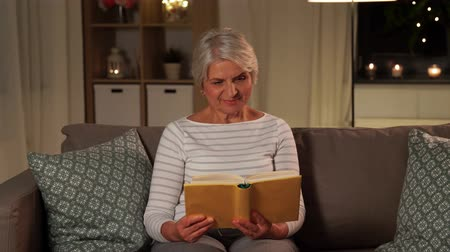 ficção : happy senior woman reading book at home in evening Vídeos