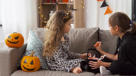 salva : girls in halloween costumes with candies at home