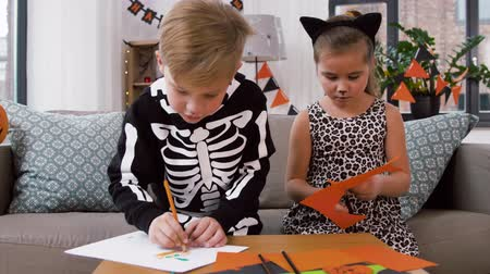 salva : kids in halloween costumes doing crafts at home