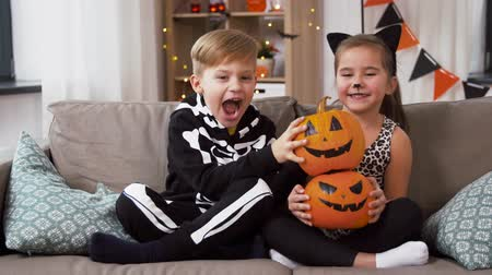 salva : kids in halloween costumes with pumpkins at home