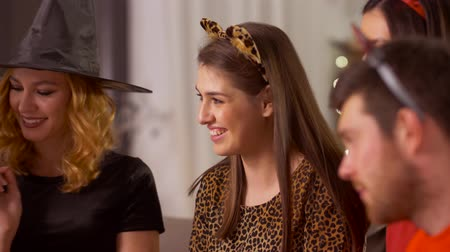 cheeta : happy friends in halloween costumes at home party
