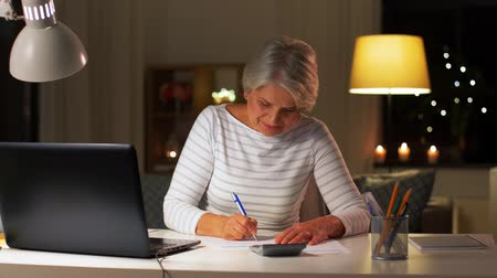 számla : senior woman filling tax form at home in evening