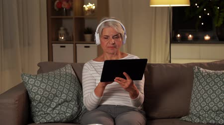 playlist : senior woman in headphones listening to music Stock Footage