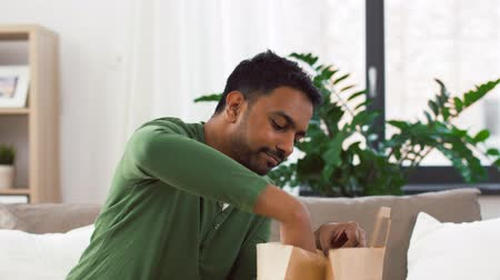 wok food : smiling indian man unpacking takeaway food at home