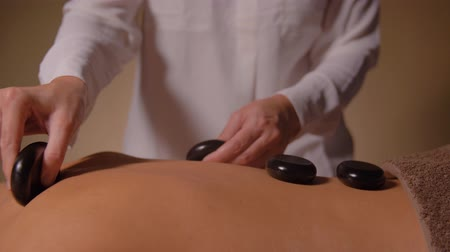 terapêutico : beautiful woman having hot stone massage at spa