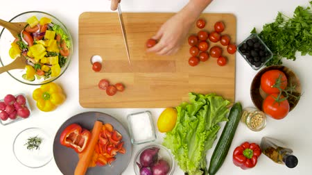 vitamin : woman chopping tomato with kitchen knife at home