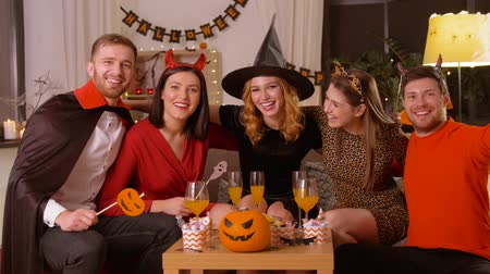 diabeł : happy friends in halloween costumes at home party