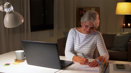 dosya : happy senior woman with laptop at home in evening