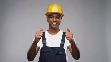 macacão : happy indian worker or builder showing thumbs up