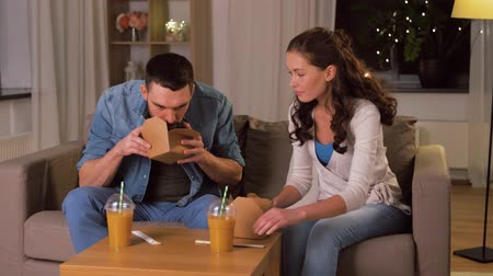 wok : happy couple eating takeaway noodles at home Stock Footage