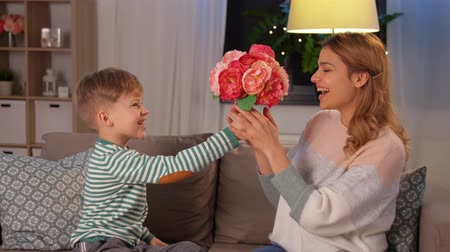 pocałunek : smiling little son gives flowers to mother at home