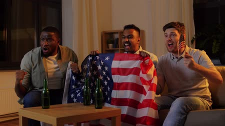 diadal : friends with american flag watching tv at night Stock mozgókép