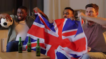 torcendo : friends with british flag watching soccer at home