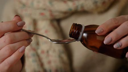 tosse : female hands pouring medicine from bottle to spoon Stock Footage