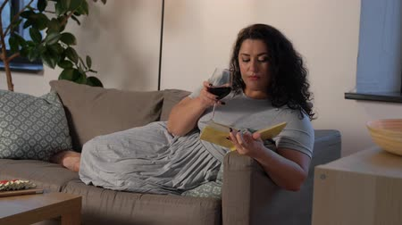 breadstick : woman reading book and drinking red wine at home