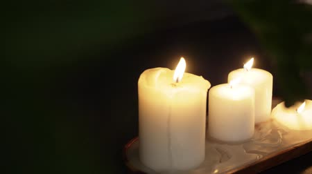 cosiness : candles burning on wooden tray in dark room