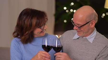 cheers : happy senior couple with glasses of red wine