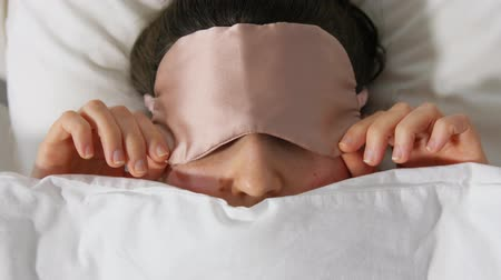 белье : woman with eye sleeping mask in bed under blanket Стоковые видеозаписи