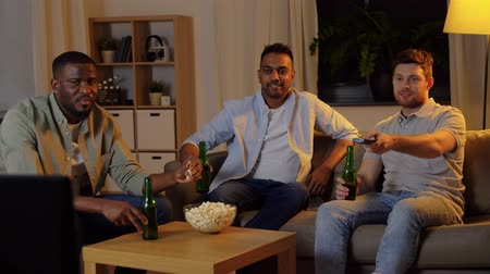 três pessoas : happy male friends with beer watching tv at home