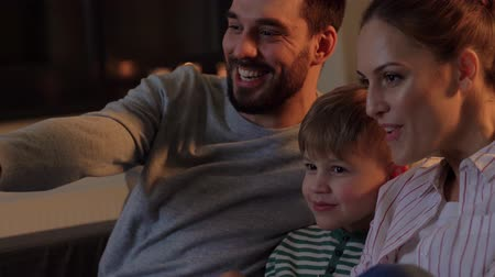 попкорн : happy family with popcorn watching tv at home